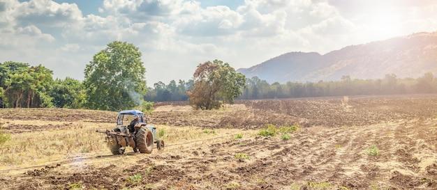 Landbouwer in tractor die en land op landbouwgebied met berg en blauwe hemel werkt voorbereidt