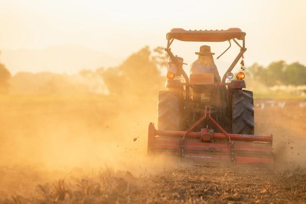 Landbouwer op grote tractor in het land om de grond voor te bereiden