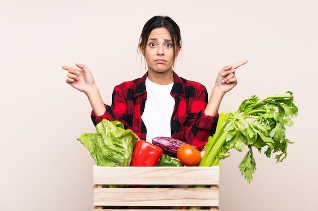 Landbouwer woman die verse groenten in een houten mand houden die aan de laterals richten die twijfels hebben