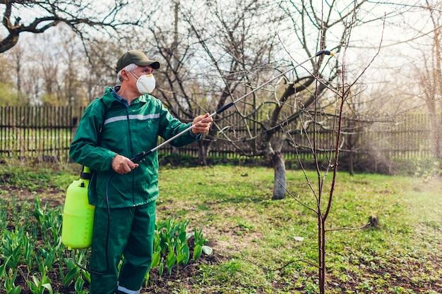 Landbouwers bespuitende boom met handmatige pesticidesproeier tegen insecten in de lentetuin