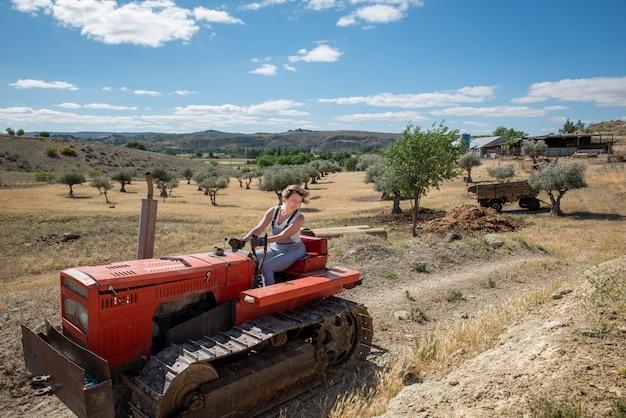 Landbouwersvrouw die een tractor op het gebied drijven