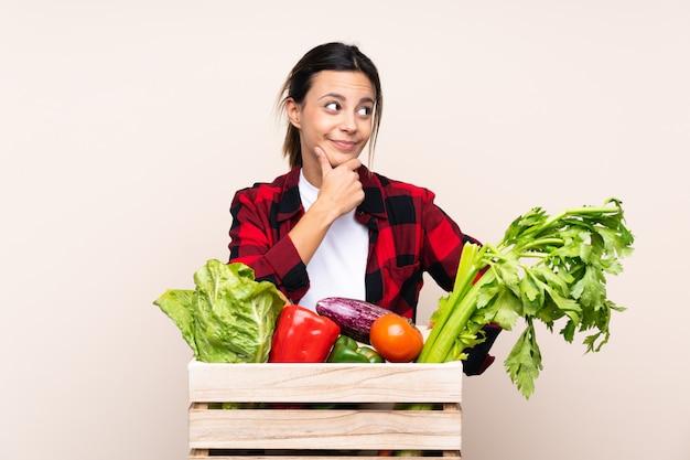 Landbouwersvrouw die verse groenten in een houten mand houden die een idee denken