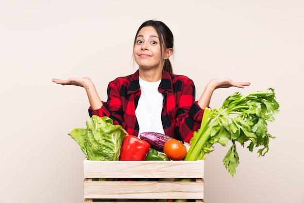 Landbouwersvrouw die verse groenten in een houten mand houden die twijfels met verwarde gezichtsuitdrukking hebben
