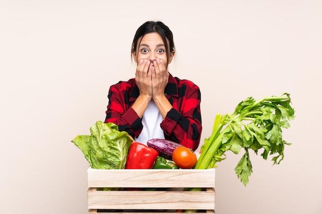 Landbouwersvrouw die verse groenten in een houten mand met verrassingsgelaatsuitdrukking houden