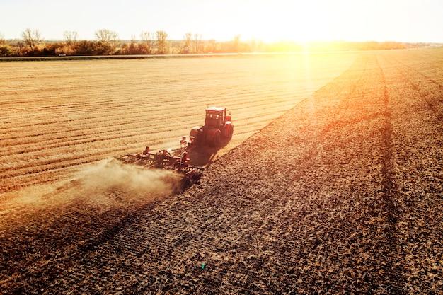 Landbouwmachine die gewassen oogst in velden. trekker trekt een mechanisme voor hooien. oogsten in de herfst in de ochtend bij zonsopgang. agribusiness in de altai regio rusland.