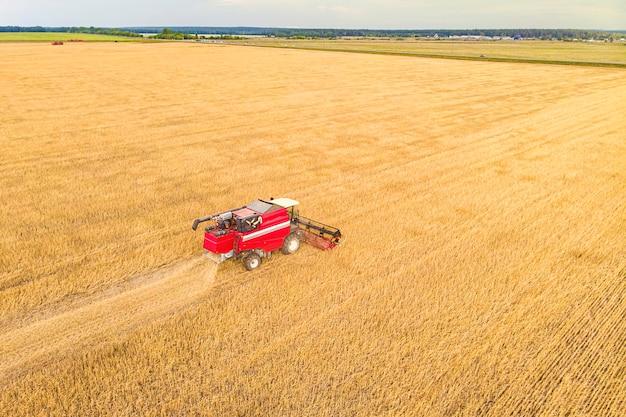 Landbouwmachine die gewassen oogst in velden. trekker trekt een mechanisme voor hooien. oogsten in de herfst in de ochtend bij zonsopgang. agribusiness in de altai regio rusland
