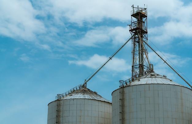 Landbouwsilo bij de fabriek van de voermolen. silo voor opslag en drogen van graan, tarwe, maïs op de boerderij. agrarische productie. tank voor winkelzaad. graanvoorraadtoren. landbouw industrie.