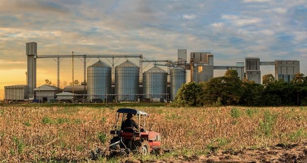 Landbouwsilo's opslagkorrels, tarwe, graan, soja, zonnebloem, blauwe hemel, landbouwbedrijftractor binnen