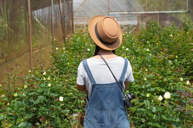 Landbouwvrouw die een tablet in de roze tuin houden.