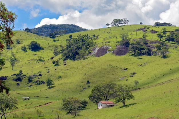 Landelijk landschap met gras, bomen en huisje op de heuvel. minas gerais, brazilië