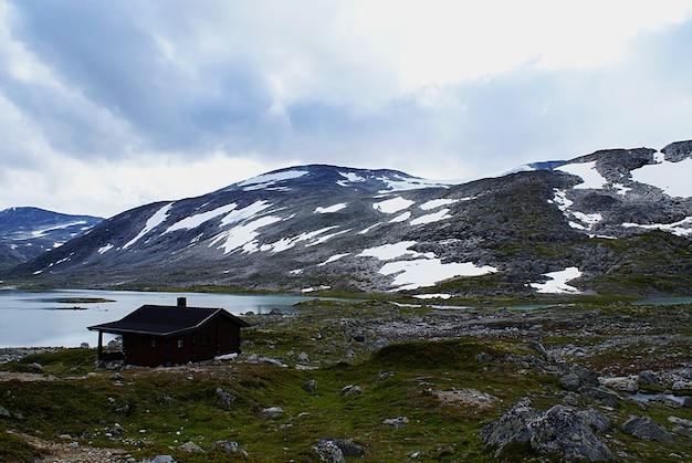 Landelijk noors huisje in de buurt van een meer, omringd door hoge rotsachtige bergen aan de atlantic ocean road, noorwegen