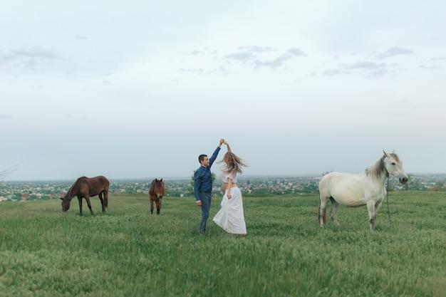 Landelijk paar op een groene weide communiceert met dieren. zwangere vrouw. therapie en ontspanning voor zwangere vrouwen.