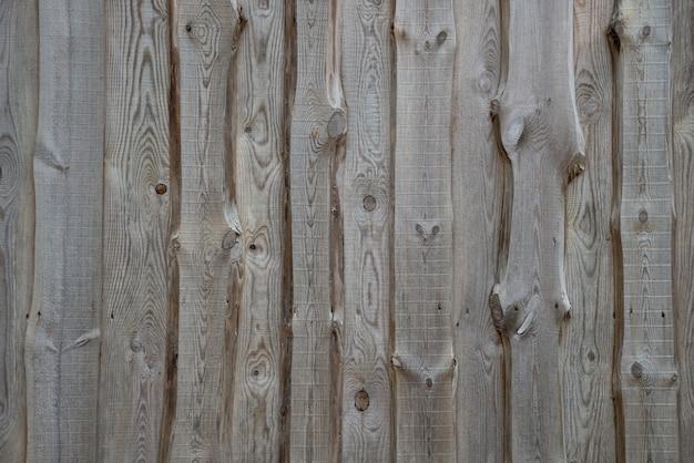 Landelijke achtergrond van houten planken met knopen in verticaal parallel patroon. houten muur gevel fragment textuur.