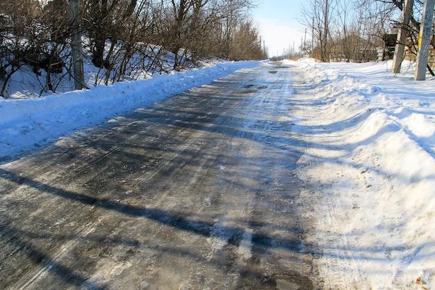 Landelijke bevroren gladde asfaltweg op de winter