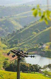 Landelijke elektrificatiepaal op het platteland met meer en bergen