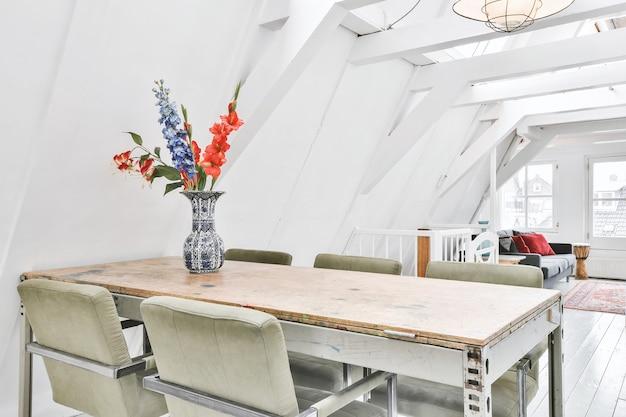 Landelijke houten tafel met groene stoelen en vaas met bloemen bovenop in studio-appartement op zolderniveau