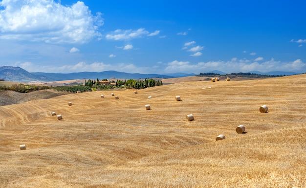 Landelijke landschappen van toscane, italië. balen en hooibergen op de heuvels en velden.