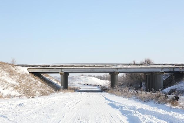 Landelijke lege weg bedekt met sneeuw op zonnige dag