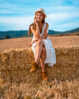 Landelijke levensstijl, een jonge blanke blonde boer met jurk in een droge tarweveld in de buurt van pamplona