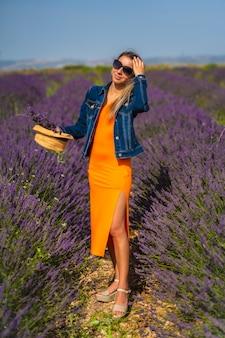 Landelijke levensstijl, jonge blonde blanke vrouw in denim jasje en oranje jurk