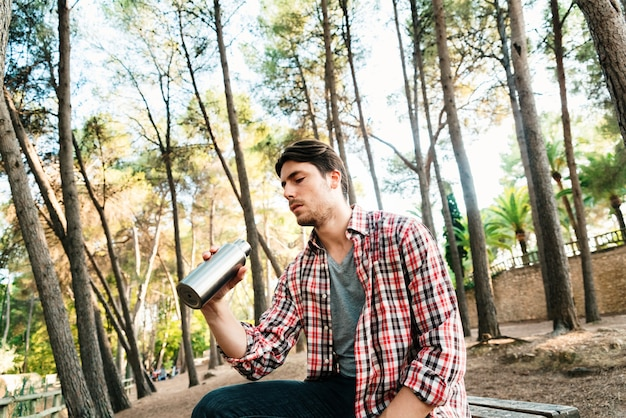 Landelijke man in een park drinkwater uit een aluminium fles.