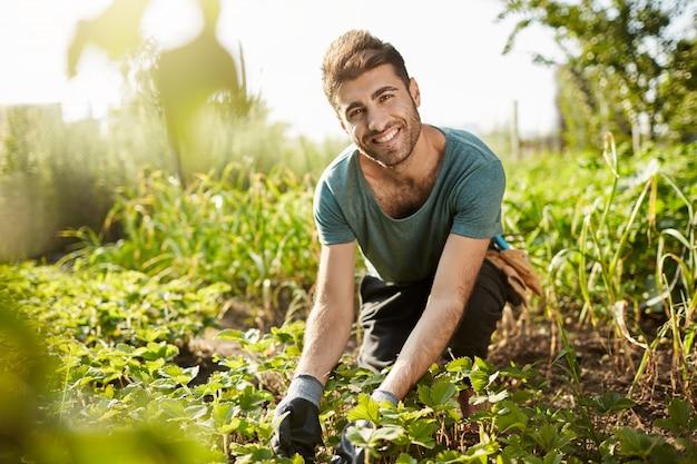 Landelijke ochtend. close up van mooie bebaarde blanke mannelijke boer in blauw t-shirt en zwarte broek glimlachen, werken op de boerderij, gewas plukken, favoriete baan.