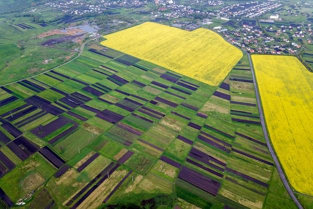 Landelijke omgeving op lente of zomerdag. luchtfoto van groene, geploegde en bloeiende velden, huis daken op zonnige dageraad. drone fotografie.