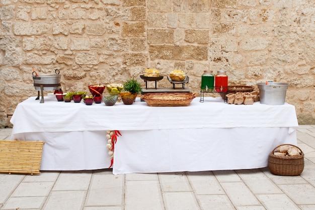 Landelijke ontvangsttafel met diverse hapjes en drankjes voor verjaardagsfeestje of bruiloft. assortiment gerechten voor vakantieviering, buitenbuffet in de buurt van stenen muur, kopieerruimte. horecaconcept
