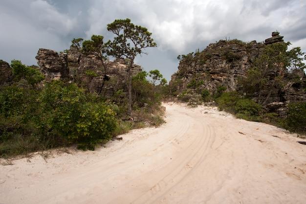 Landelijke onverharde weg met zand en zandsteen rotsen