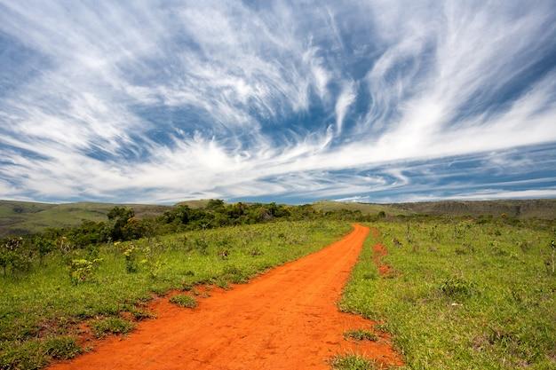 Landelijke oranje onverharde weg met blauwe hemel en verre horizon