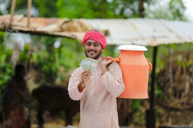 Landelijke scène: indiase melkboer die geld toont op zijn boerderij