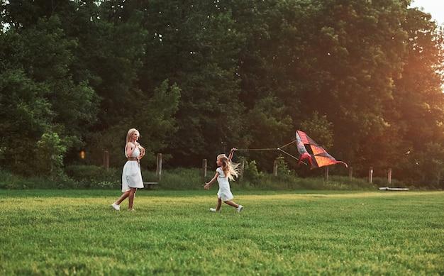 Landelijke scène. moeder en dochter hebben plezier met vlieger in het veld. prachtige natuur.