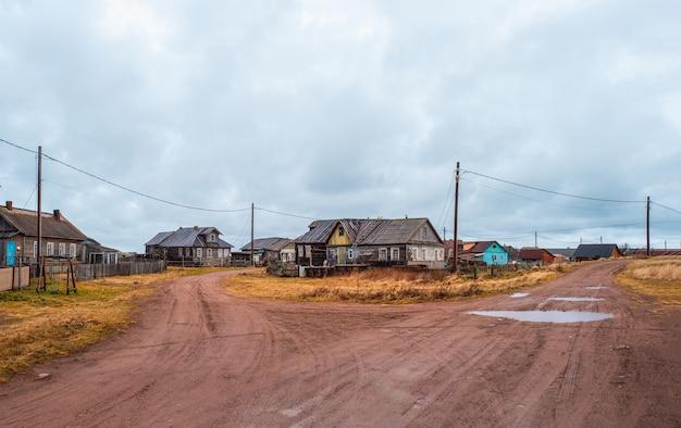 Landelijke splitsing van de weg. een klein authentiek dorpje aan de witte zeekust. kashkarantsy visserij collectieve boerderij. kola-schiereiland. rusland.