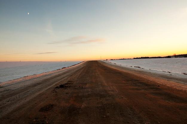 Landelijke weg die door landbouwvelden loopt, vervangen door witte sneeuw na een sneeuwval. op de rijbaan ligt veel vuil en land van gesmolten sneeuw