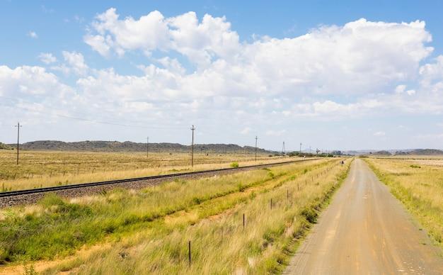 Landelijke weg naast een spoorweg in een veld