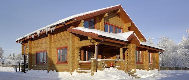 Landhuis, blokhut van gekleurd hout met lichtbruine schaduw, dak van huis is bedekt met sneeuw, zonnige winterdag.