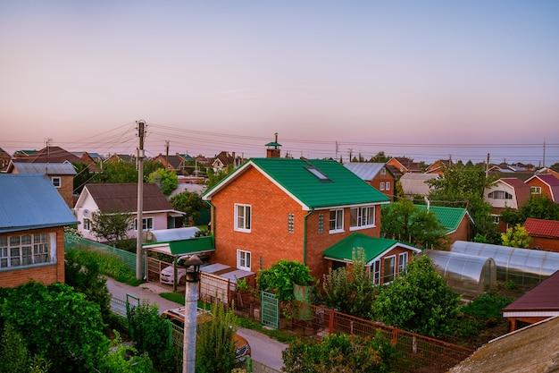 Landhuizen met percelen voor een moestuin russische zomerhuisjes vanaf een hoogte bij zonsondergang