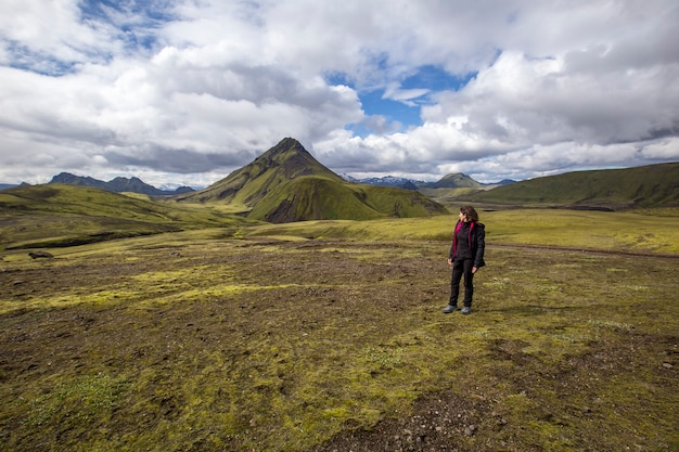 Landmannalaugar, ijsland ã'â »; augustus 2017: een jonge vrouw in het ongelooflijke landschap van de landmannalaugar-trekking en een berg op de achtergrond