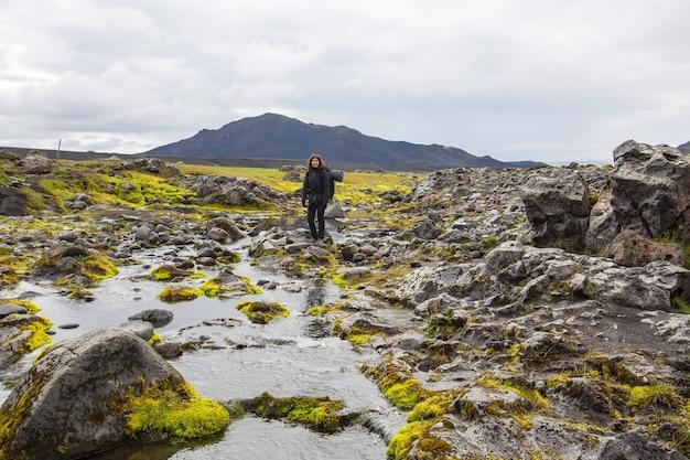 Landmannalaugar, ijsland ã'â »; augustus 2017: een jonge vrouw steekt een rivier over tijdens de landmannalaugar-trekking
