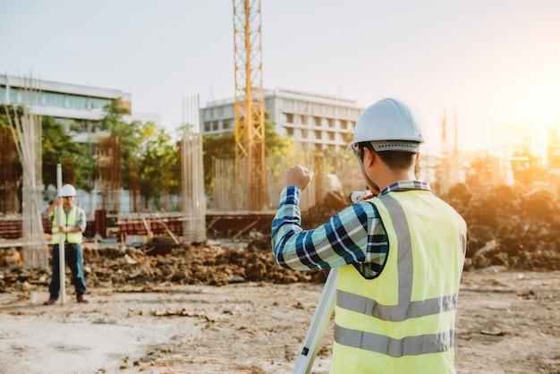 Landmeetkundige ingenieurs werken samen met theodoliet op de bouwplaats.