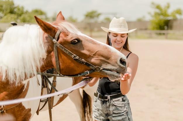Landmeisje die een paard op een boerderij voeden