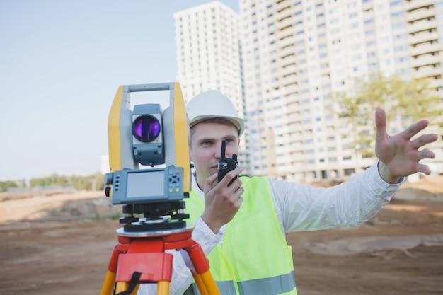 Landmeter-ingenieur in beschermende kleding met geodetische apparatuur