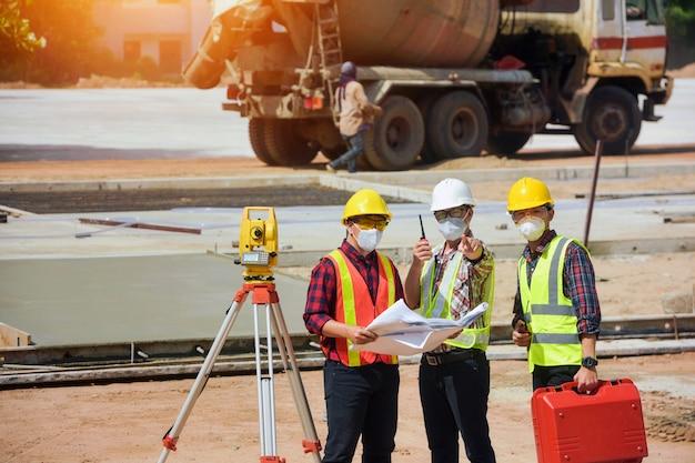 Landmeter ingenieur werknemer maken meten met theodoliet op wegwerkzaamheden. survey engineer in bouwplaats.