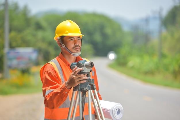 Landmeter-ingenieursarbeider die meten met theodoliet maakt op wegenwerken.survey-ingenieur op de bouwplaats.