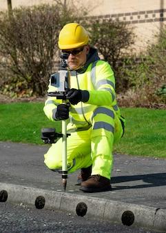 Landmeter voert een eerste onderzoek uit van de wegniveaus en stoepranden voor de start