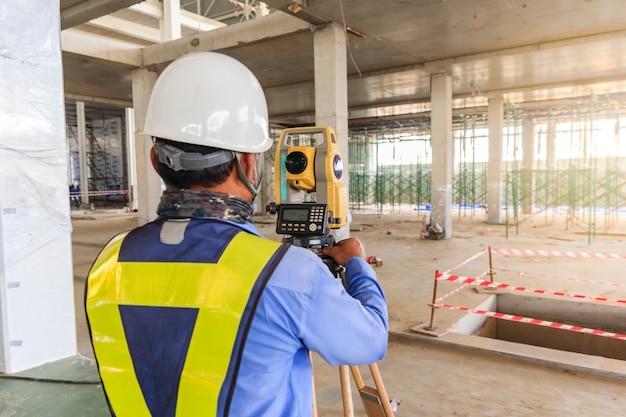 Landmetersingenieurwerker die het meten met theodolietmateriaal maken bij bouwwerf.