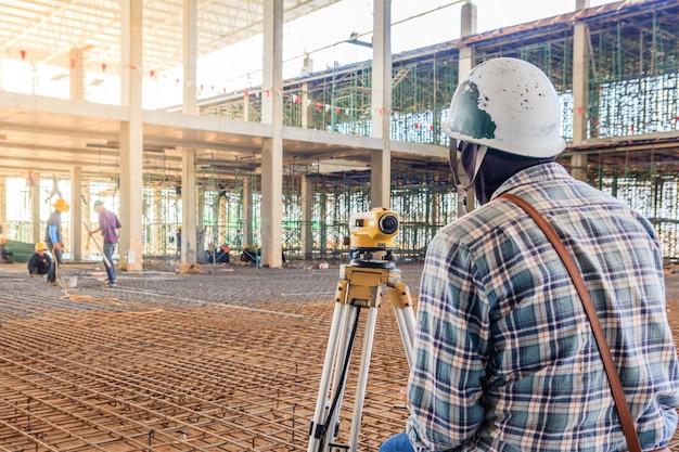 Landmeterwerknemer maakt het meten met theodolietmateriaal bij fabrieksbouwwerf.