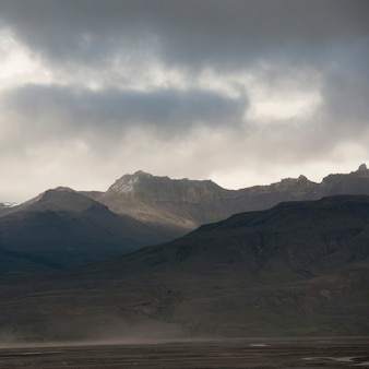 Landschap, bergketen onder stormachtige luchten