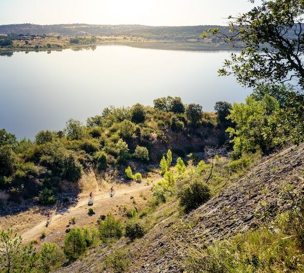 Landschap bij zonsopgang op een meer met zonnevlammen aan de horizon, reflecties in het water en een heldere zonnige dag. lente natuurscène. guadalix, madrid.