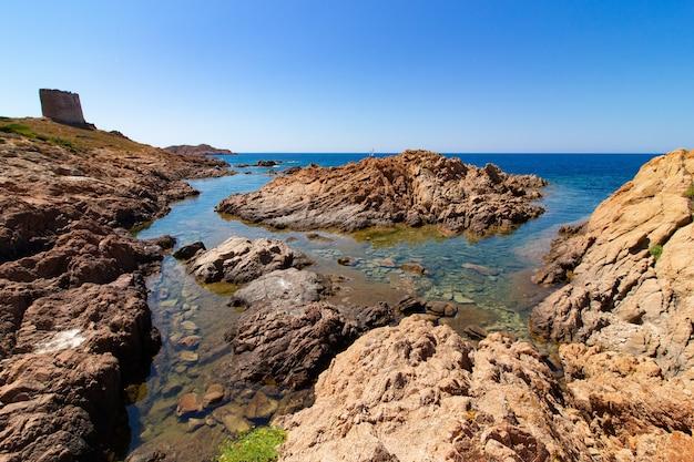 Landschap dat van grote rotsen in een blauwe oceaan met een duidelijke blauwe hemel is ontsproten